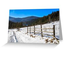 fence on snowy mountain slope near the forest in winter Greeting Card