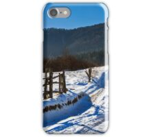 snowy road to coniferous forest in mountains iPhone Case/Skin