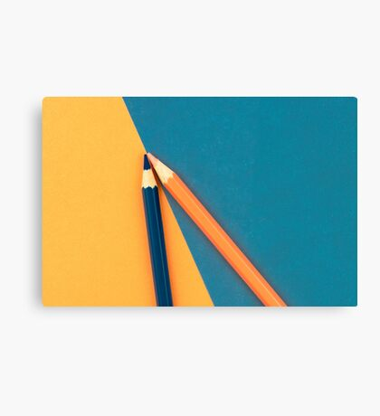 Orange and Dark Blue coloured pencils and paper Canvas Print