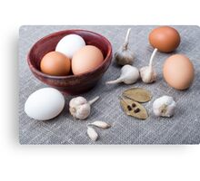 Chicken eggs and garlic and spices on the kitchen table Canvas Print