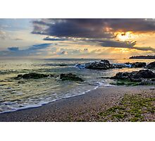 morning sun rays illuminate sandy beach with small rocks Photographic Print