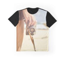 Young woman hold camera at the beach Graphic T-Shirt