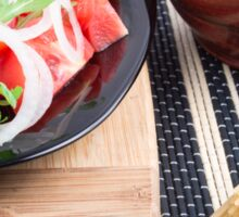 Black plate with fresh salad of tomatoes, onions and arugula Sticker