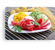 White plate with slices of fresh tomatoes, cucumber, corn, arugula and onions Canvas Print