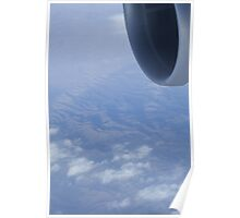 Jumbo jet airplane wing engine in flight flying over mountains and blue sky photograph Poster