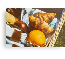 Picnic Basket With Orange Juice Bottle, Apples, Peaches, Oranges And Croissants On Green Grass In Spring Metal Print