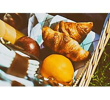Picnic Basket With Orange Juice Bottle, Apples, Peaches, Oranges And Croissants On Green Grass In Spring Photographic Print