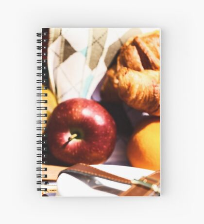 Picnic Basket With Orange Juice Bottle, Apples, Peaches, Oranges And Croissants On Green Grass In Spring Spiral Notebook