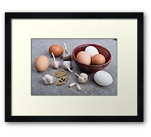 Raw eggs and garlic and spices on the kitchen table Framed Print