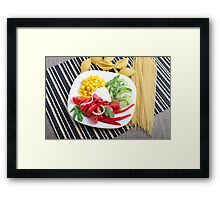 Top view of a white plate with slices of fresh vegetables Framed Print