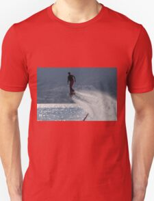 Flyboarder followed by spray over backlit sea Unisex T-Shirt