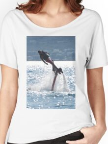 Flyboarder leaning into turn over backlit waves Women's Relaxed Fit T-Shirt