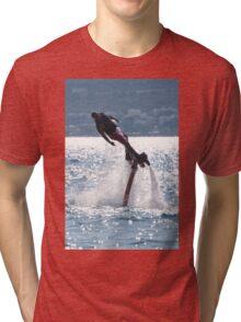 Flyboarder leaning into turn over backlit waves Tri-blend T-Shirt
