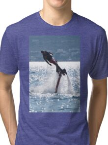 Flyboarder leaning into turn over backlit waves Tri-blend T-Shirt