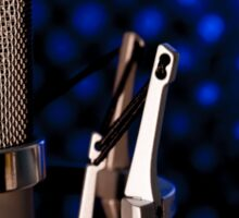 Silver microphone on black and blue background Sticker