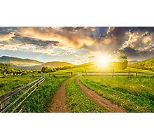 road and wooden fence on hillside at sunset Photographic Print
