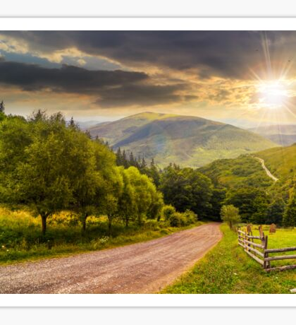 fence near road down the hill with  forest in mountains at sunset Sticker