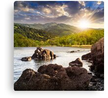 lake shore with stones near forest on mountain at sunset Canvas Print