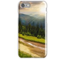 road through conifer forest in mountains at sunset iPhone Case/Skin