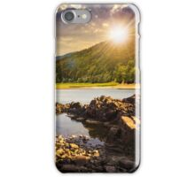 lake shore with stones near pine forest on mountain at sunset iPhone Case/Skin