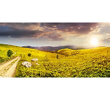 road on hillside meadow in mountain panorama at sunset Photographic Print