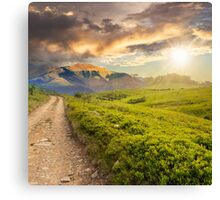 gravel road to high mountains at sunset Canvas Print
