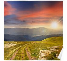 road among stones on the hillside at sunset Poster