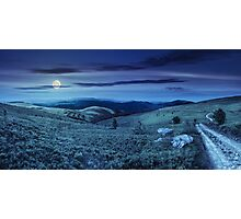road on hillside meadow in mountain panorama at night Photographic Print