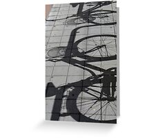 Shadows of bicycles on the asphalt Greeting Card