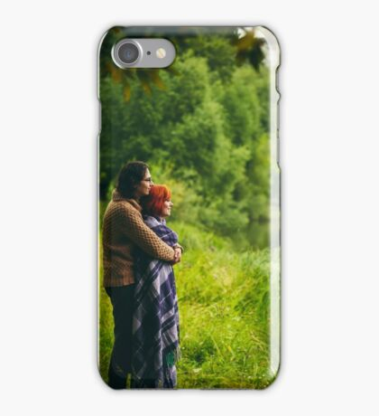 Young happy couple standing near water in green forest iPhone Case/Skin