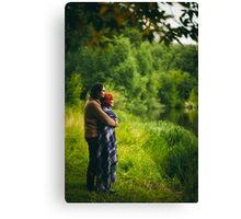 Young happy couple standing near water in green forest Canvas Print