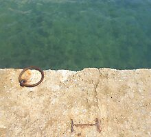 Teal waters and a rusty ring in a dock by by-jwp