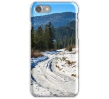 fence by the road to snowy forest in the mountains iPhone Case/Skin