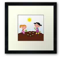 Two happy kids watering and planting plants in the garden Framed Print