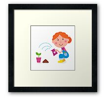 Small girl is watering plant in the garden Framed Print