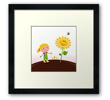 Spring gardening : Gardener child with sunflower in the garden Framed Print