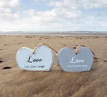 couple of inscribed wooden love hearts in the sand by morrbyte