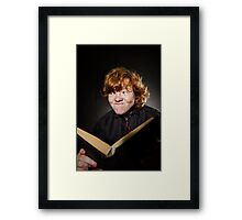 Freckled red-haired teenage boy reading book, education concept, isolated on black background Framed Print