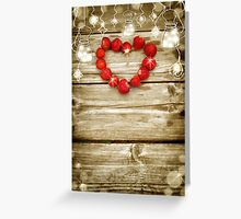 Old grunge wooden board with light bulb border, strawberry in the shape of a heart. Greeting Card
