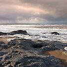 black rocks on Ballybunion beach by morrbyte