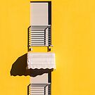 Window with sunshade on a yellow wall by Silvia Ganora