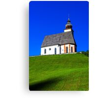 Beautiful little church in Alps. Sunny day, green grass on the hill and blue sky. Austria. Canvas Print