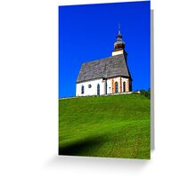 Beautiful little church in Alps. Sunny day, green grass on the hill and blue sky. Austria. Greeting Card
