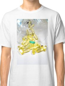 Several yellow gelatin pills with one unique green one Classic T-Shirt