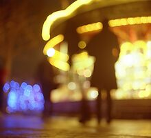 People walking in street at night with fairground lights in Hasselblad vintage camera analogue film photo by edwardolive