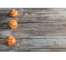 Oranges with clove spice on old wooden table. Photographic Print