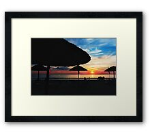 Sunset at the beach with sun umbrellas Framed Print