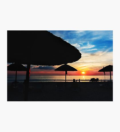Sunset at the beach with sun umbrellas Photographic Print
