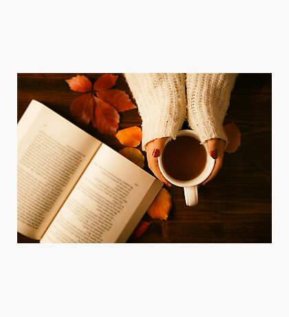 Woman hands holding teacup and opened book seen from above Photographic Print