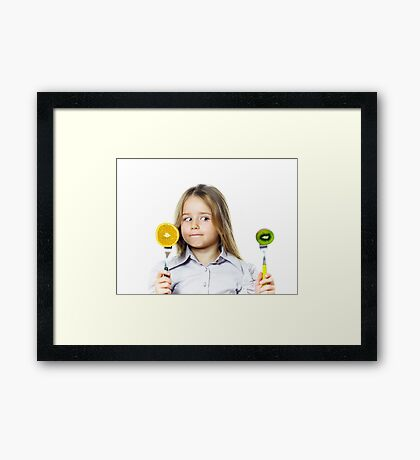 Funny little girl selecting between kiwi and orange, isolated on white background Framed Print
